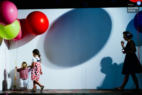 Documentary Wedding Photograph in London | Image contains: ballons, shadow, wall, kids, color, woman