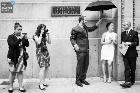 Chicago Wedding Photographer | Elopement Image contains: groom, bride, black and white, building, umbrella, women, cameras
