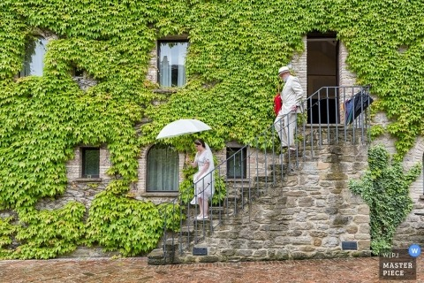 Perugia Documentary Wedding Photographer | Image contains: bride, stairs, outdoor, building, ivy, umbrella