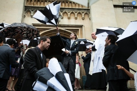London Wedding Photographer | Image contains: church, wedding guests, umbrellas, outdoors, color