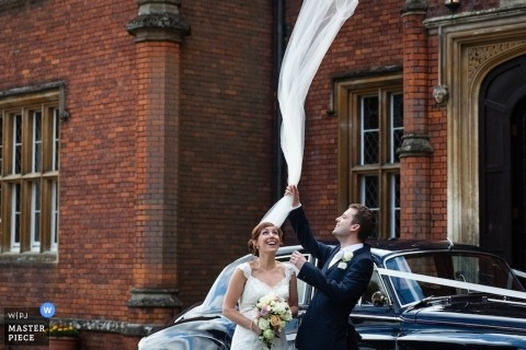 Wedding Photographer in London | Image contains: bride, groom, flying veil, car