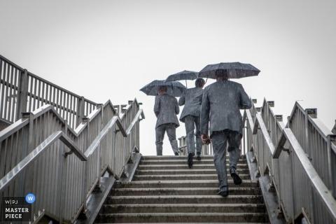 London Wedding Photographer   Image contains: rain, umbrellas, groomsmen, stairs, outdoors, color, raining