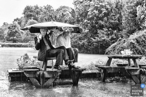 Documentary Wedding Photograph in Leicestershire   Image contains: rain, umbrella, down, pour, soaked