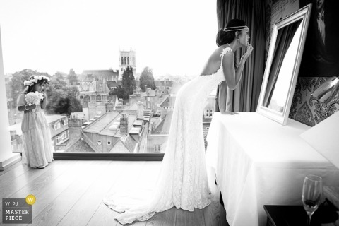 Hertfordshire  Wedding Photography | Image contains: black and white, getting ready, bride, flowergirl, city view, window