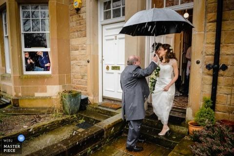 Scotland Documentary Wedding Photographer | Image contains: rain, pre-ceremony, color, father, umbrella, bride, house