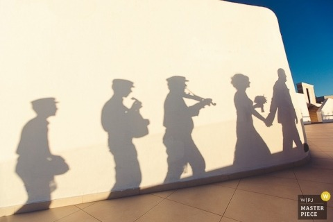 Saint-Petersburg bride and groom photography | shadows on the wall of musicians following the ceremony parade