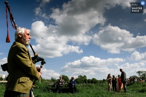 Documentary Wedding Photograph in London | Image contains: sky, clouds, guests, bagpipe