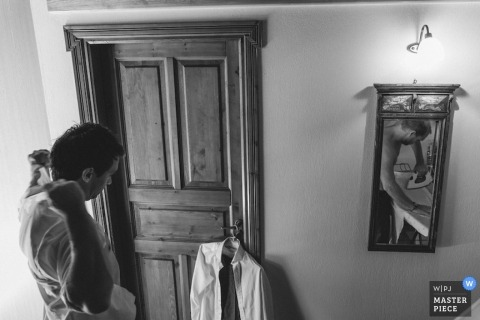 Greece Wedding Photography | Image contains: black, white, getting ready, mirror, door, groom, ironing, iron