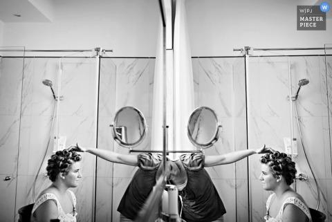 Slovénie Photographe de mariage documentaire | L'image contient: noir et blanc, se préparer, bigoudis, miroir, reflet, salle de bain
