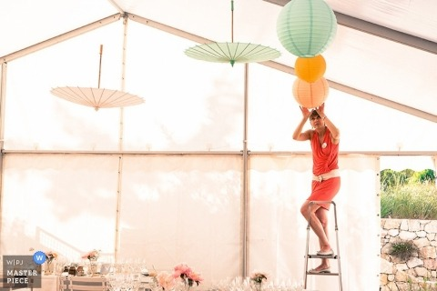 Documentary Wedding Photograph in Paris   Image contains: getting ready, reception room, color, lanterns, umbrellas, ladder, tent