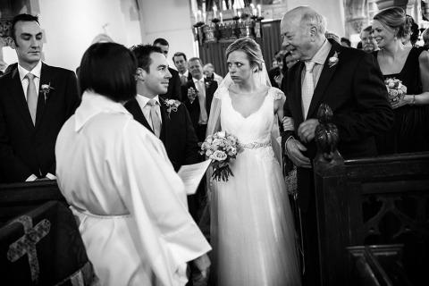 Fotografia di matrimonio nel Regno Unito di una cerimonia con la sposa in chiesa in bianco e nero.