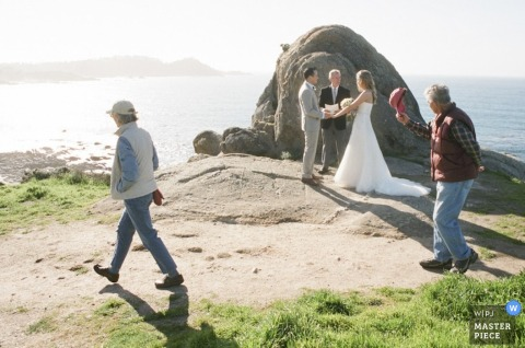 A couple stands near a rock by water during their elopement ceremony as two gentlemen walk by, one man tipping his hat.