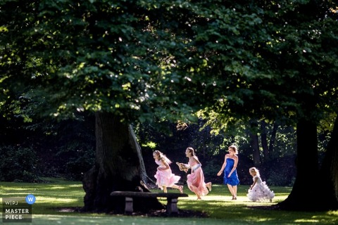 Lower Saxony wedding picture of girls running and playing in the grass under the trees
