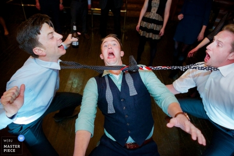 Idaho Wedding Photojournalism | Image contains: reception, ties, limbo, groom, groomsmen