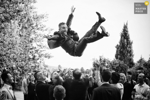 Arezzo Documentary Wedding Photographer for Tuscany | Image contains: groom, toss, outdoors, trees, black, white, guests