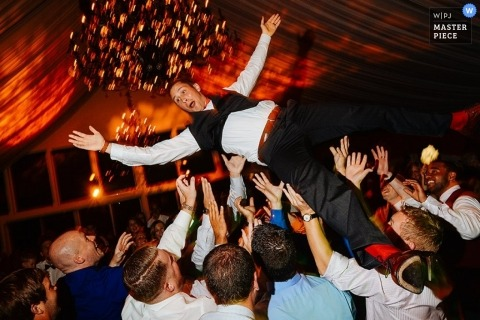 Wedding Photographer in Pennsylvania | Image contains: tent, groom, toss, wedding guests, red