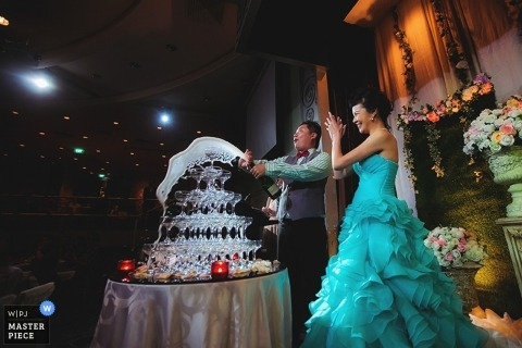 Documentary Wedding Photographer | Image contains: champagne, glasses, tower, bride, groom, laughing, blue dress