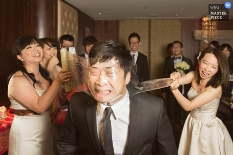 Wedding Photojournalism | Image contains: groom plastic face stretch game