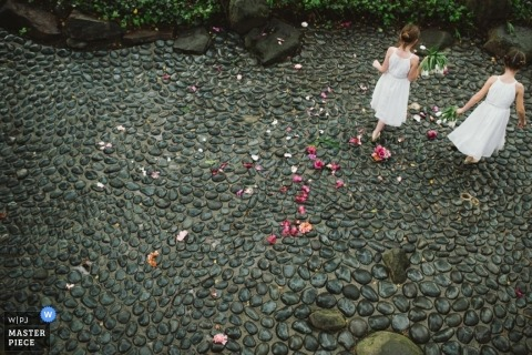 California - Northern Wedding Photojournalism | Image contains: flowergirls, stone, pattern, flower pedals, outdoors