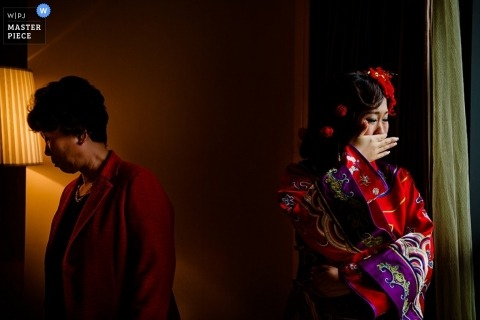 Documentary Wedding Photographer in Tianjin | Image contains: crying, window, dress, mother, indoors, getting ready