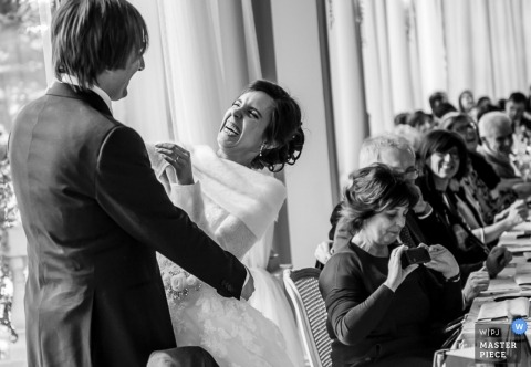 Lecco Documentary Wedding Photographer | Image contains: black and white, bride and groom, reception, wedding guests, embrace, banquet, tables