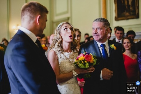 East Midlands Wedding Reportage Photography | Image contains: flowers, bride, father, groom, ceremony, color, eye-rolling