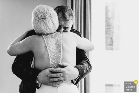Derbyshire Wedding Reportage Photography | Image contains: father, bride, crying, hug, window, black, white