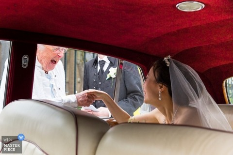 Zuid Holland Wedding Photographer | Image contains: bride, car, veil, red, vintage, holding hands, groom