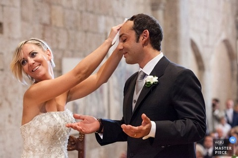 Rome Wedding Photographer | Image contains: bride wiping sweat from groom's brow during ceremony