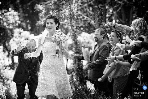 Arezzo Wedding Photography in Tuscany | Image contains: groom, bride, rice, ceremony, flowers, guests, black, white