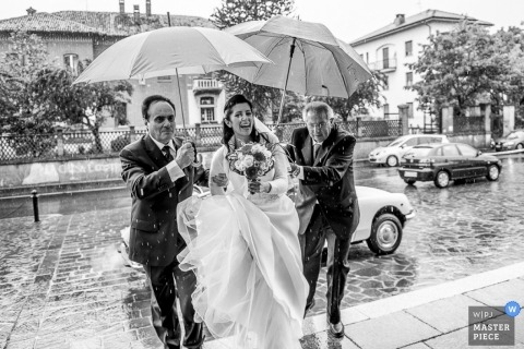 Lecco Documentary Wedding Photographer | Image contains: umbrellas, ceremony, father, bride, flowers, rain, outdoors