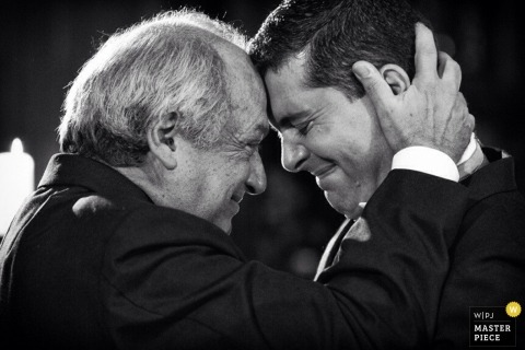 Brazil Wedding Photojournalism | Image contains: father, groom, crying, hug, black, white