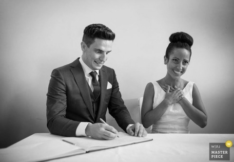 London Wedding Reportage Photo | Image contains: black and white, bride, groom, ceremony, book signing