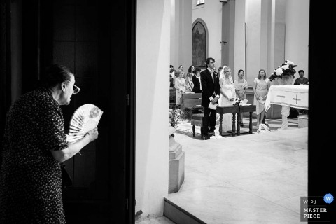 Tuscany Documentary Wedding Photographer | Image contains: church, ceremony, bride, groom, women, hand fan