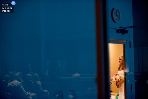 Documentary Wedding Photographer in Pennsylvania | Image contains: bride, blue, door, flowers, dress, wedding guests