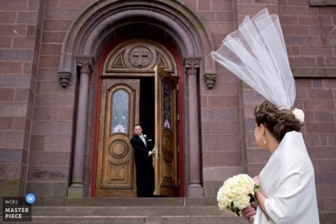 Massachusetts bride has veil flying away, upward outside of church.