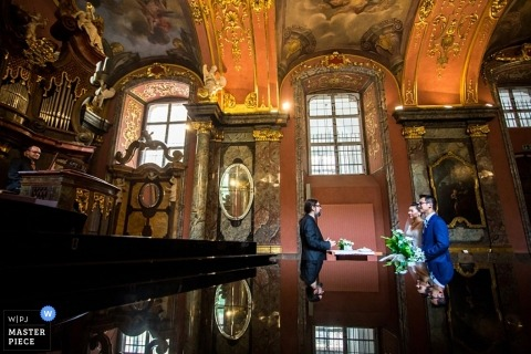 Prague Wedding Photojournalism | Image contains: ceremony, church, bride, groom, pastor, table, reflection, orange