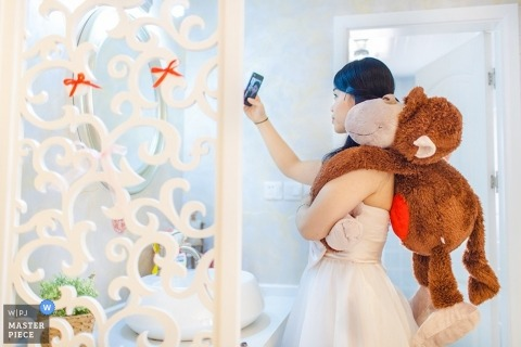 Shanghai Wedding Photographer | Image contains: selfie, stuffed monkey, bride, getting ready, restroom, door