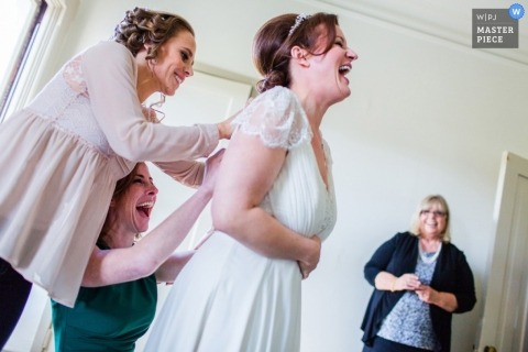 San Francisco Wedding Photojournalism | Image contains: bride, dress, buttons, bridesmaids, laughing, getting ready