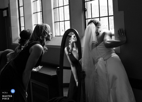 Documentary Wedding Photographer in Toronto | Image contains: bride looking out window while getting ready.