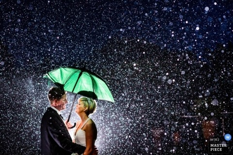 Wedding Photography in Guernsey | Image contains: portrait, bride, groom, lit, night, umbrella, rain