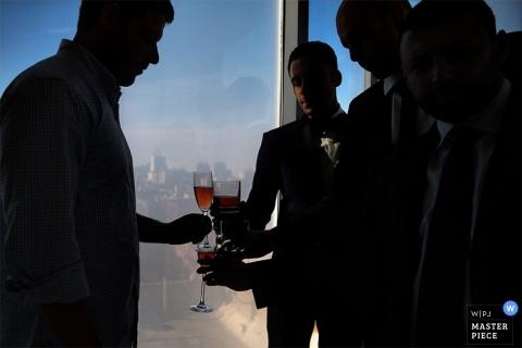 Bronx Creative Wedding Photographer | Image contains: groom, groomsmen, wedding reception, toast, city, window