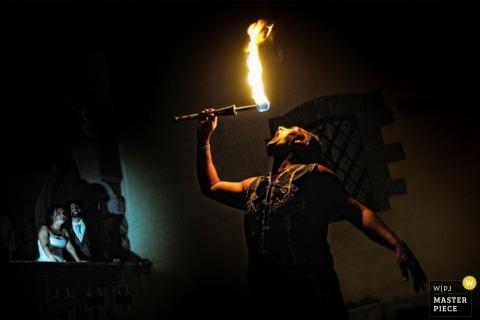 Toscane Bruiloft Fotojournalistiek | Afbeelding bevat: fakkel, vuur, bruidegom, bruid, receptie, donker