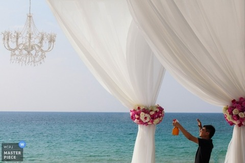 Phuket Beach Ceremony Documentary Wedding Photographer | Image contains: flowers, chandelier, curtains, sea, outdoors