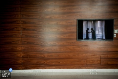 An old fashioned kissing of the hand moment captured in the reflection of a television on a wood paneled wall with a glimpse of a view behind the Bangkok wedding couple