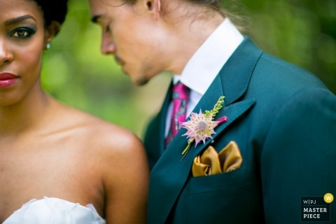 A New Rochelle wedding close up in Westchester County where the bride looks straight into the camera and the groom in a teal suit and pink tie is turned to the side with his eyes closed