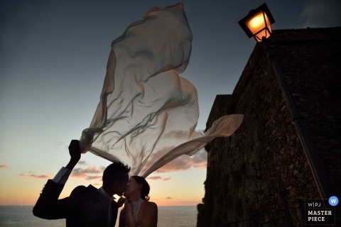 A wedding image showing the bride and groom kissing in the outdoor evening air of Florence Tuscany while holding the bride's veil as it lifts up in the wind