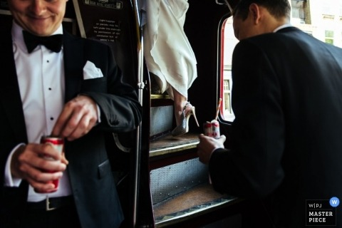 A bride and her beer touting groom step onto their red wedding bus in London England making for a unique celebration in an image featuring mainly the groom and only the bride's legs