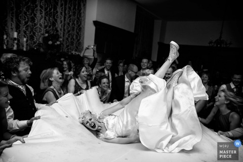 A Devon bride takes a tumble at her reception in England in a black and white wedding reportage image