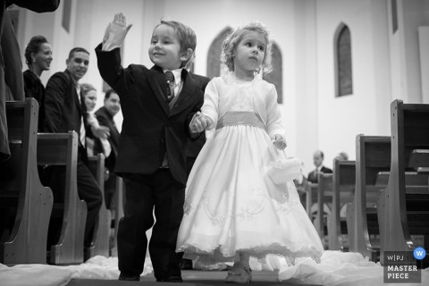 A black and white photo of a confident page boy, and uncertain flower girl as they walk down the aisle in Rio Grande do Sul, Brazil.